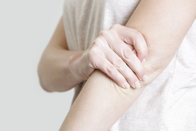 Woman holding her elbow