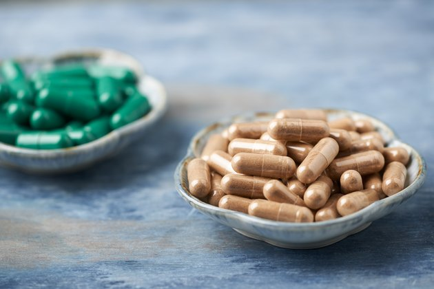 Green Tea and L - Carnitine capsules. Concept for a healthy dietary supplementation. Rustic wooden background. Copy space.