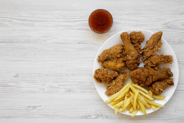 Tasty fried chicken legs, spicy wings, French fries, chicken tenders and sauce on white plate over white wooden background, top view. Flat lay, overhead, from above. Copy space.