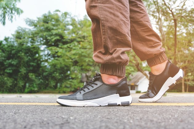 Man walking on a road while wearing walking shoes