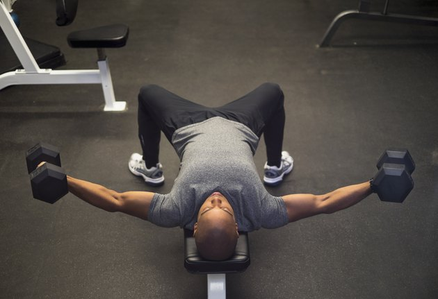 Man in the gym doing dumbbell chest flyes