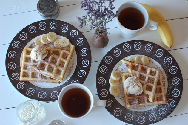 two white ceramic mugs beside plate of belgian waffles