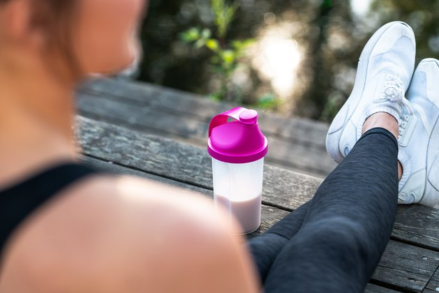 Woman resting and drinking a protein shake after her exercise