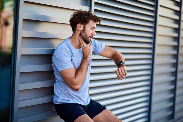 Man taking his pulse to measure heart rate during exercising outside
