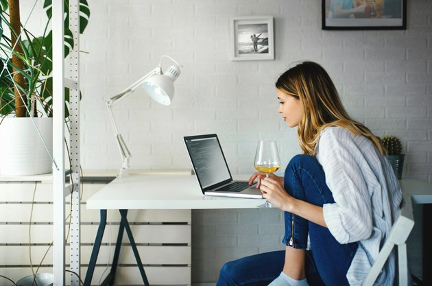 Young woman working from home with a glass of wine