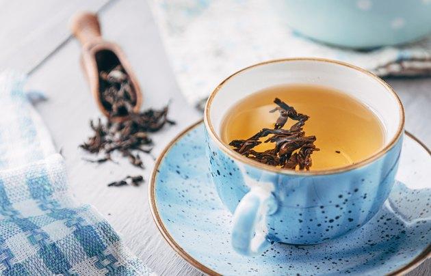 Cup of black tea on table