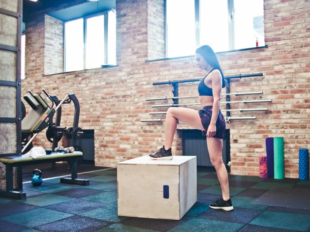Workout concept. Brunette woman in sportswear preparing to jump on the wooden box in the gym. Functional training
