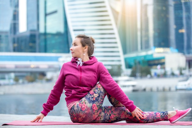 Young woman in Ardha Matsyendrasana pose against city and river