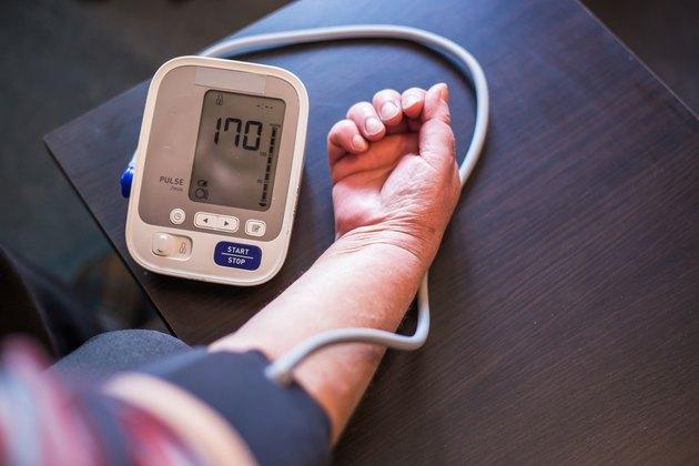 Senior woman measures high blood pressure at home