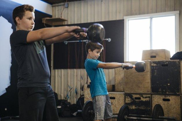 Boys lifting kettlebells at gym