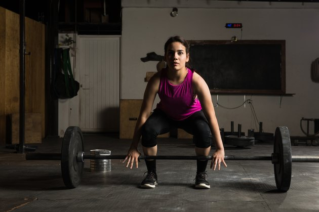 Young woman about to lift a barbell to perform deadlift variations