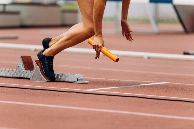 start female runner with baton in hand relay race running