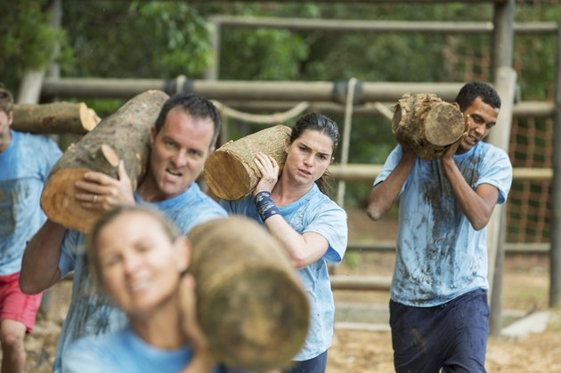 Determined team carrying logs on boot camp race course