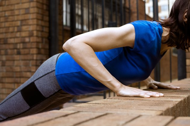 Young adult white woman doing bench push ups outside, selective focus