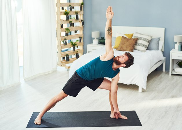 man with beard wearing blue tank top practicing yoga on a black mat in his bedroom