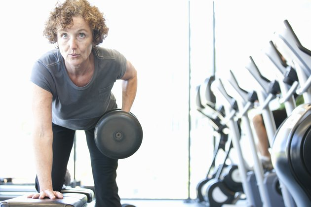 Woman lifting weights in gym during a cardio and strength workout