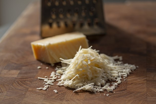 Grated italian parmesan cheese on wooden chopping board with a block of Parmesan and a grater in the background to bread proteins on a low-carb diet