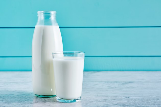 Bottle of milk and a glass full of milk on a wooden table against turquoise wooden background. Close up view.