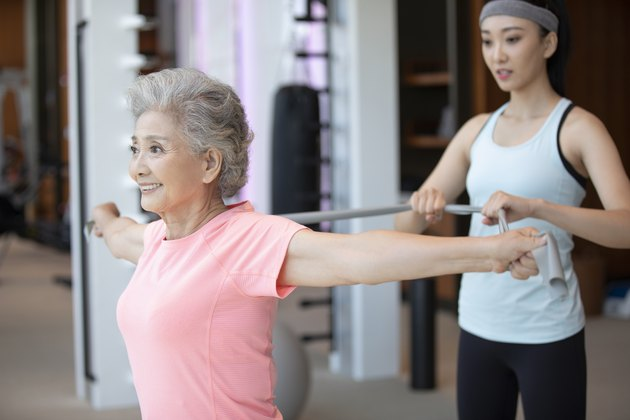 Senior Chinese woman working out with personal trainer at gym