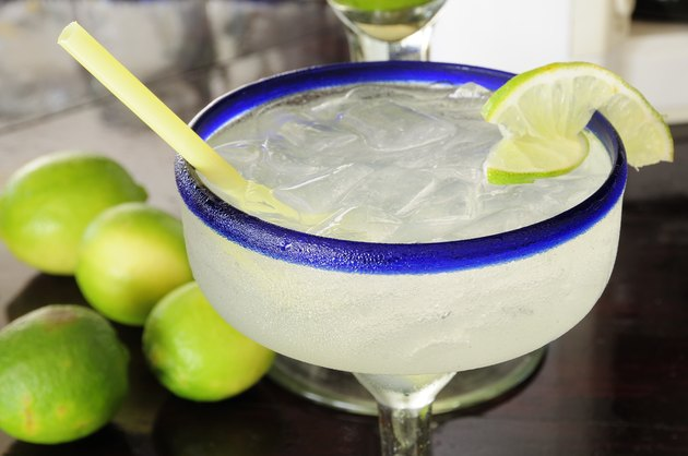 Mexico, Jalisco, Puerto Vallarta, Frosted glass of a margarita cocktail served with ice and slice of lime with whole limes at side