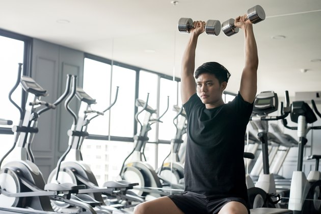 Young man shoulder pressing dumbbells.