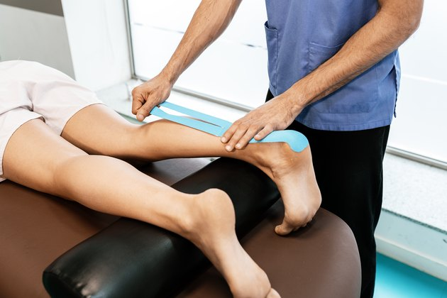 Physiotherapist giving calf therapy to a woman