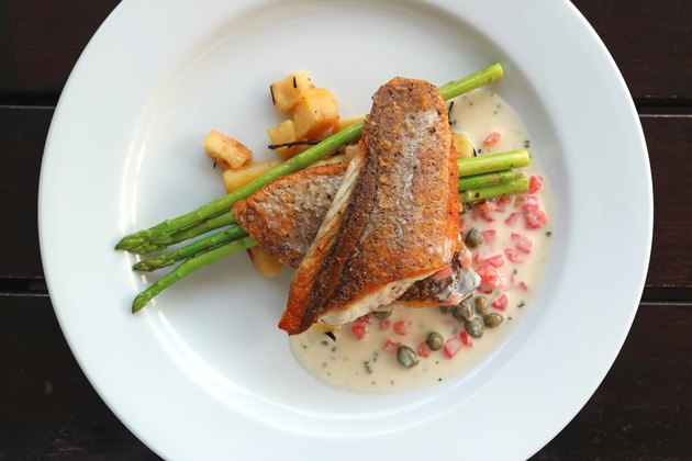 Top view of pan seared sea bass with tomato caper mustard cream sauce