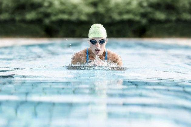 Young woman swimming in swimming pool, breast-stroke swimming