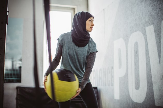 Woman doing HIIT workout with medicine ball at the gym