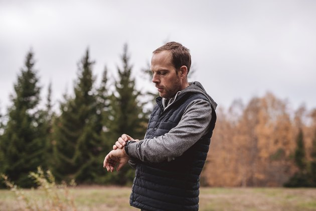 Man with fitness tracker walking outdoors in nature