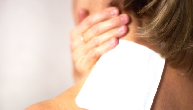 Woman with Heating Pad on Stiff Neck Close-Up