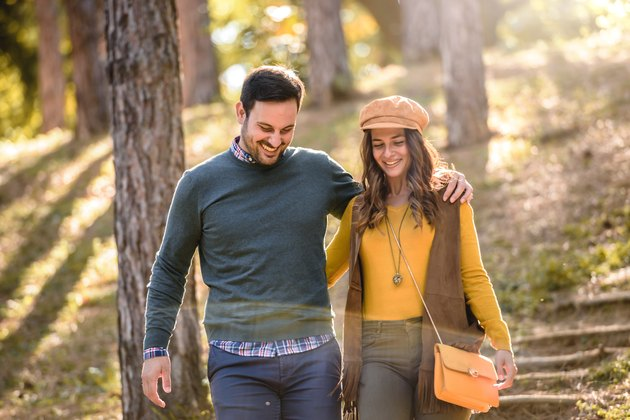 Beautiful smiling love couple walking in colorful autumn forest park