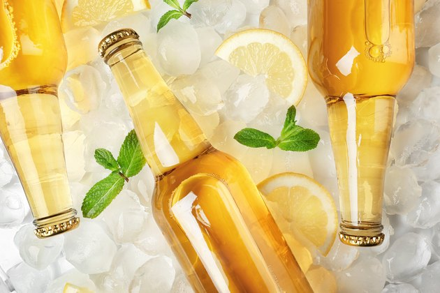 Bottles of lemonade on ice background