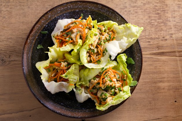 Lettuce wraps with chicken, carrot, peanuts and scallion. Stuffed iceberg lettuce leaves with chicken