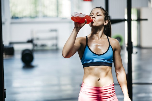 women dressed in athletic clothing drinks flavored water.
