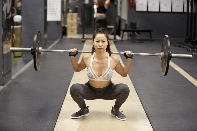 Woman squatting with barbell on her shoulders in a fitness gym.