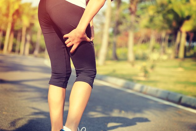woman runner hold sports injured leg on tropical park trail