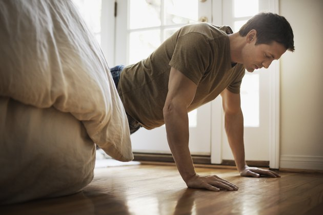 Man doing push-ups in bedroom at home