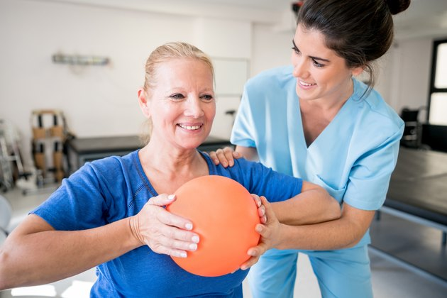 Senior woman patient at physical recovery therapy exercising with a ball and therapist helping her