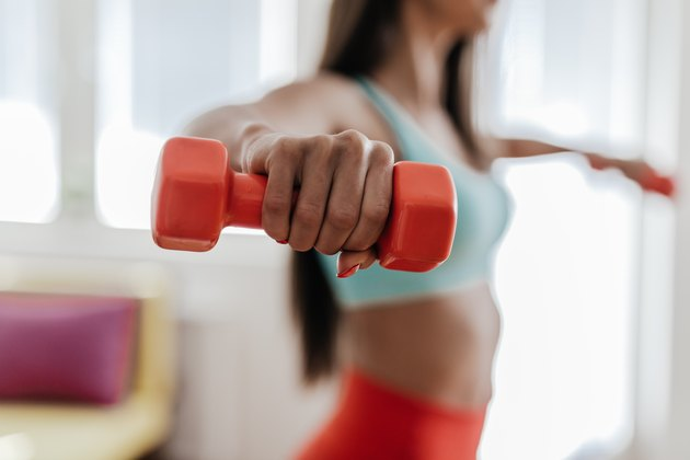 Young woman exercising with her weights in the living room
