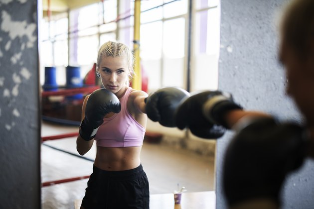 Woman standing in front of mirror and boxing.