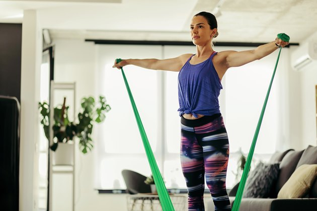 Athletic woman exercising with a resistance band at home.