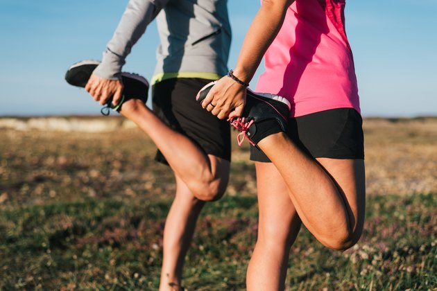 Sporty couple stretching legs outdoors before trail running workout outdoors