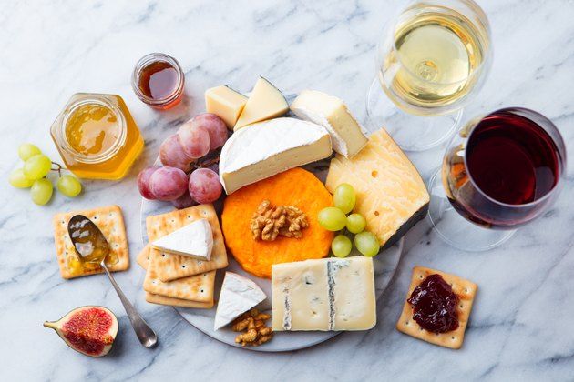 Assortment of cheese, grapes with red and white wine in glasses. Marble background. Top view.