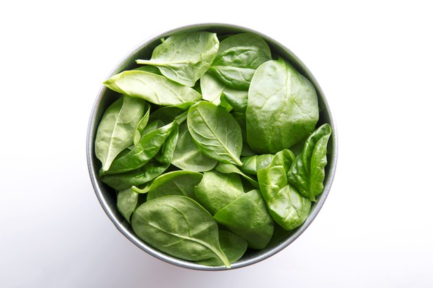 Directly Above Shot Of Spinach Leaves In Container Over White Background