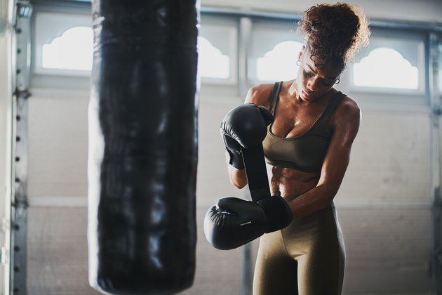 woman covered in sweat from boxing punching bag taking off gloves
