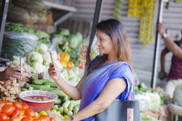 Woman at a food market using a food tracking app on her smartphone