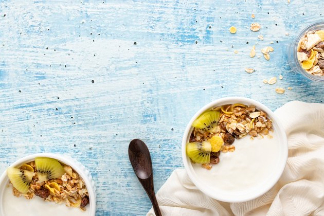 Top view of yogurt in bowl with granola,fresh kiwi  on wooden table. Health food concept.