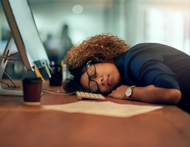 A young woman sleeping at her desk at work