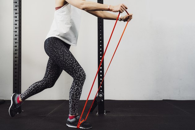 Unrecognizable woman in sports clothes working out with elastic band